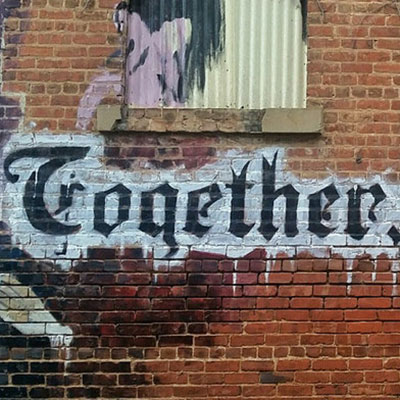 Together we words spray painted on a building