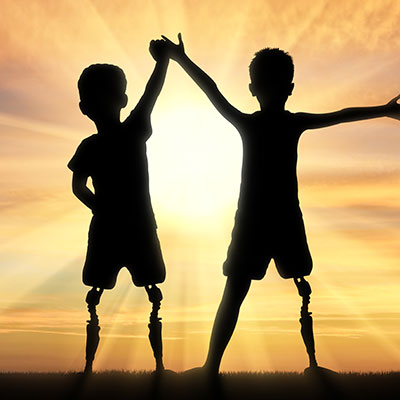 Two kids with prosthetic legs in the sunset